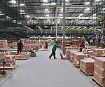 Interior large warehouse with people working, moving freight with hand carts.