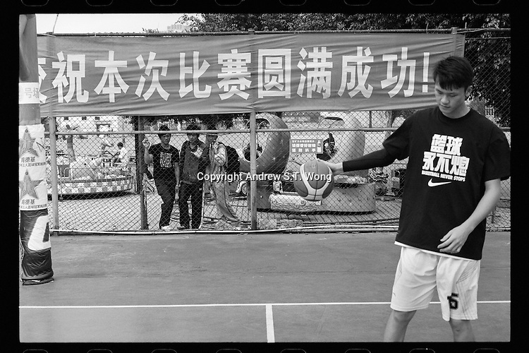 A basketball player of Dongguan Guangming Middle School warms up before a match of the China High School Basketball League in Zhuhai, Guangdong province, November 2011.