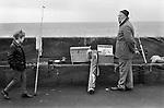 Elderly man 1970s UK, on holiday fishing with small portable radio 70s Bridlington Yorkshire 70s England