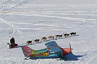 Paul Johnson runds down the Innoko River at Shageluk past pilot Dave Looney's Maule airplane on Saturday during Iditarod 2011