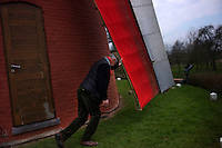 The blades of a Tombeelmolen windmill are pushed to a start by Freddy Deweer in Outrijve, Belgium on March, 31 2013.