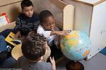 Education Preschool 4 year olds three boys looking at globe in classroom