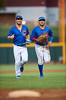 AZL Cubs 2 outfielders Brandon Vicens (15) and Abraham Rodriguez (12) jog off the field between innings of an Arizona League game against the AZL Reds on July 23, 2019 at Sloan Park in Mesa, Arizona. AZL Cubs 2 defeated the AZL Reds 5-3. (Zachary Lucy/Four Seam Images)