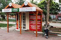 Un vieil homme assis devant une petite bibliothèque exterieure, distribuant des livres sur l'islam.