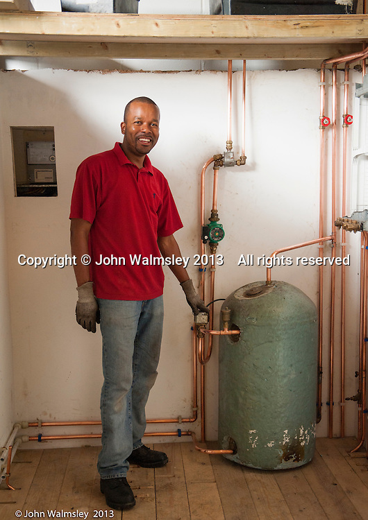 Trainee plumber and his completed project, Able Skills training centre, Dartford, Kent.