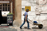 A man pushes a wheelbarrow through the streets of Prague.