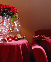 A side table with a red tablecloth decorated with tea lights glass baubles and red roses