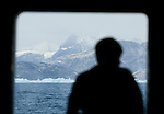 A figure is silhouetted in a ship window while on an Arctic expedition in Eastern Greenland. IN the background, the mountains of Greenland.