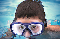 Young boy wearing scuba mask while swimming in a pool.