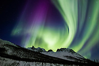 Aurora borealis swirls across the sky over the Brooks Range, Snowden mountain, Arctic Alaska.