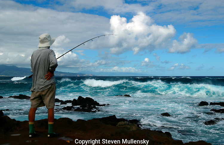 A solitary fisherman tries for the catch of the day off Maui.