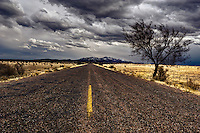 A long, straight, rough blacktop road leading to the Ortiz Mountains in the distance under a stormy sky.