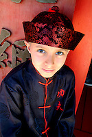 A young boy dressed in traditional attire outside the Chinese temple at Hawaii Plantation Village
