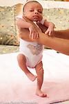 Newborn baby girl 12 days old held upright reflex stepping