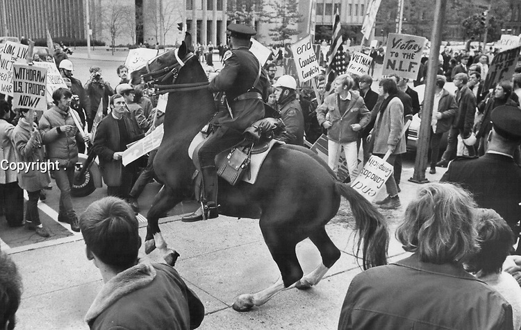 Mounted Police officer is surrounded by demonstrators protesting the Viet Nam war; outside the Toronto U.S. consulate on University Ave. in 1968. <br /> <br /> <br /> Griffin, Doug<br /> Picture, 1968,