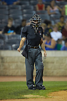 Home plate umpire Kelvis Velez makes a fist after having been hit in the forearm by a foul ball during the South Atlantic League game between the Lexington Legends and the West Virginia Power at Appalachian Power Park on June 7, 2018 in Charleston, West Virginia. The Power defeated the Legends 5-1. (Brian Westerholt/Four Seam Images)