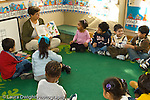 Preschool Headstart 4 year olds New York City circle time female teacher reading book to group of children horizontal
