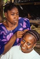 Abidjan, Ivory Coast, Cote d'Ivoire.  Braiding Hair in the Cocody Market.