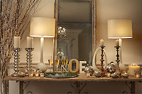 An antique side table in the living room is decorated with candles and mercury glass baubles in celebration of Christmas