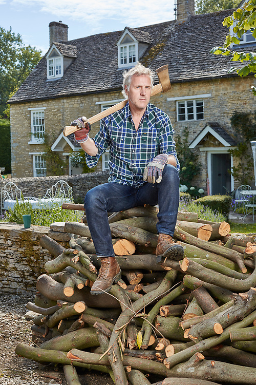 Photo John Angerson. 200722<br /> Times Writer Simon Mills with his stack of wood he has been chopping during lockdown. At his home in Oxfordshire.
