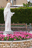 A statue of the Madonna in a flower bed in front of the church. Medugorje pilgrimage village, near Mostar. Medjugorje. Federation Bosne i Hercegovine. Bosnia Herzegovina, Europe.