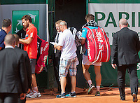 France, Paris , May 24, 2015, Tennis, Roland Garros, Igor Sijsling (NED) (R) is leaving the court while Ernest Gulbis (LAT) signs autographs<br /> Photo: Tennisimages/Henk Koster