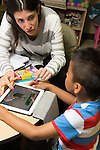 Education Preschool 4-5 year olds SEIT (Special Education Itinerent Teacher) working with child in classroom, using tablet activity to engage attention