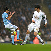 Jesus Navas competes with Ki Sung-Yueng during the Barclays Premier League Match between Manchester City and Swansea City played at the Etihad Stadium, Manchester on 12th December 2015