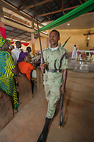 """Nigeria. Abakaliki State. Uburu Amach. St. Patrick's Catholic Church. An Igbo man in green uniform from the Organization """"Man of Order and Discipline Movement of Nigeria (M.O.D)"""" carries a sword in his right hand and walks out of the church at the end of the mass celebration for the 25th Priesthood Anniversary of Reverend Father Edward Inyanwachi. The Organization """"Man of Order and Discipline Movement of Nigeria (M.O.D)"""" is a Catholic voluntary organization. It was founded in the year 1983 by a Priest of the Catholic Church Most Rev. Monsignor Patrick O. Achebe. 14.07.19 © 2019 Didier Ruef<br /> <br /> ."""
