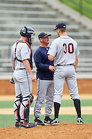 Virginia Cavaliers assistant coach Karl Kuhn (center) has a chat with pitcher Connor Jones (30) and catcher Robbie Coman (8) during the game against the Wake Forest Demon Deacons at Wake Forest Baseball Park on May 17, 2014 in Winston-Salem, North Carolina.  The Demon Deacons defeated the Cavaliers 4-3.  (Brian Westerholt/Four Seam Images)