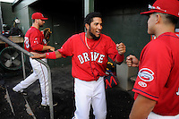 Second baseman Wendell Rijo (11) of the Greenville Drive gets a fist bump as he exits the field in a game against the Lexington Legends on Sunday, August 31, 2014, at Fluor Field at the West End in Greenville, South Carolina. Rijo is the No. 18 prospect of the Boston Red Sox, according to Baseball America. Greenville won, 3-2. (Tom Priddy/Four Seam Images)