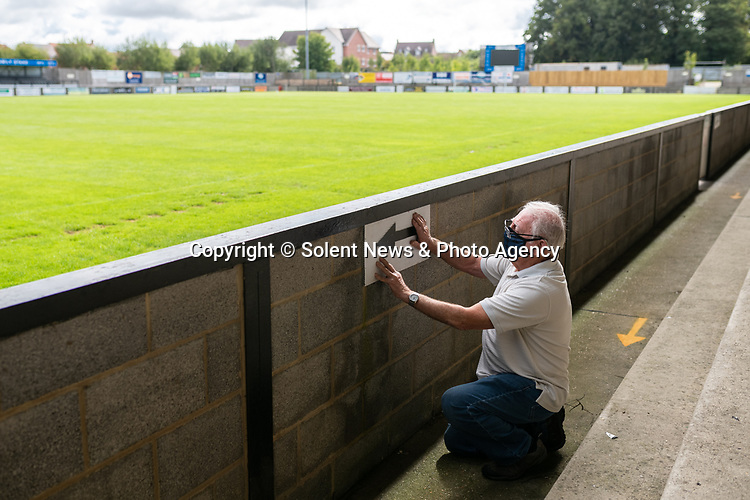 Pictured: Volunteer maintenance worker Ray Neal adjusts an arrow on the wall during preparations ahead of crowds being welcomed back into sporting events at The Raymond McEnhill Stadium in Salisbury, Wilts.<br /> <br /> Inline with the governments easing of lockdown restrictions, Salisbury Football Club are preparaing to welcome back 30% of their fans as of this Monday, August 31st. <br /> <br /> Salisbury FC play in Southern League Premier Division South, or step 3 of the non-league football ladder. <br /> <br /> © Jordan Pettitt/Solent News & Photo Agency<br /> UK +44 (0) 2380 458800