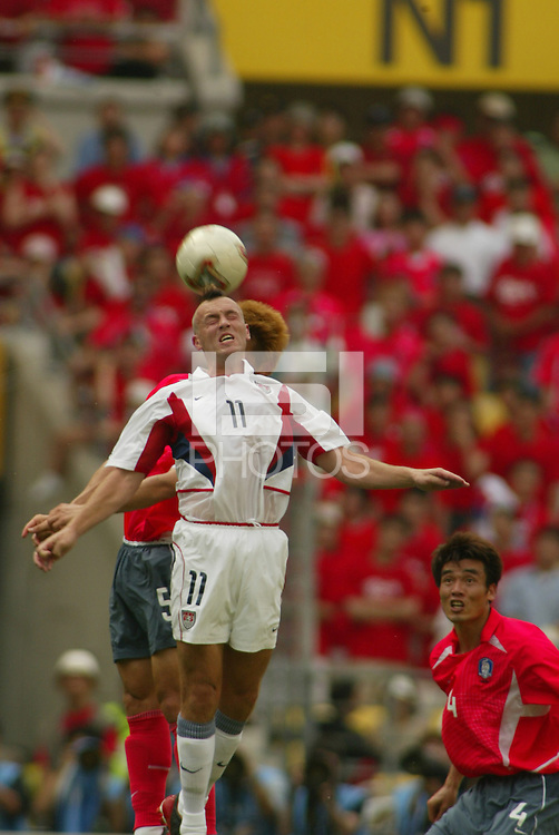 Clint Mathis jumps for a header. The USA tied South Korea, 1-1, during the FIFA World Cup 2002 in Daegu, Korea.