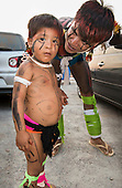 A Kuikuro man with traditional face and body paint talks affectionately to his son at the first ever International Indigenous Games, in the city of Palmas, Tocantins State, Brazil. The games will start with an opening ceremony on Friday the 23rd October. Photo © Sue Cunningham, pictures@scphotographic.com 21st October 2015