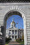 Concord, NH state house viewed through stone arch memorial.