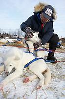 Veterinarian William Liska of Texas examines a Robert Nelson Jr. dog at the Shageluk checkpoint on Saturday morning    Iditarod 2009