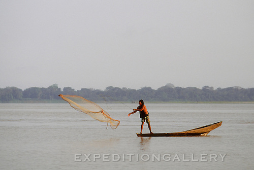 A native man balances on the gunwales of a wooden dugout canoe as he throws a fishing net into the waters of the Amazon River in Peru, South America. [No Model Release]