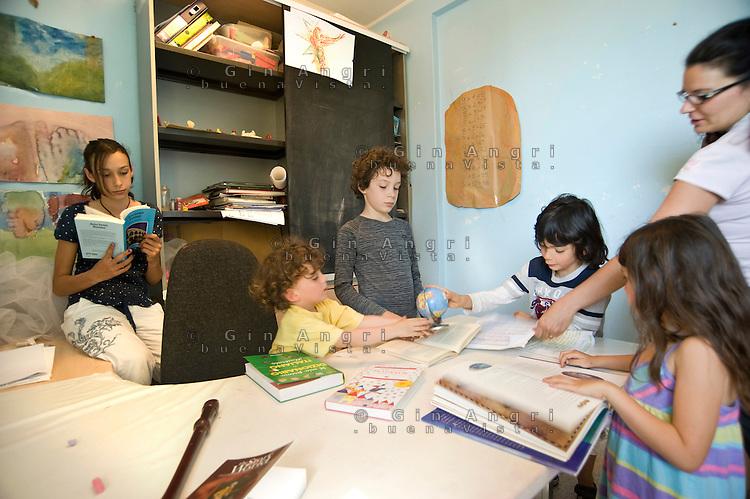 homeschooling, educazione parentale. Erika De Martino controlla i lavori dei vari bambini