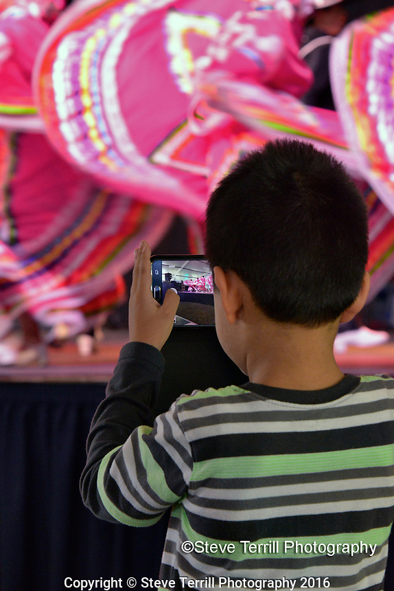 Small boy taking video of dancers at Cinco De Mayo Festival in Portland Oregon