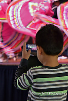 Small boy taking video of dancers at Cinco De Mayo Festival in Portland Oregon