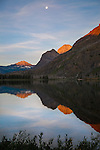 Full moon at sunrise over Red Eagle Lake in Montana's Glacier National Park. Sun touching mountain peaks at sunrise.
