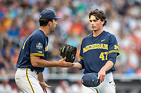 Michigan Wolverines pitcher Tommy Henry (47) is greeted by teammate Jack Bredeson (34) during Game 6 of the NCAA College World Series against the Florida State Seminoles on June 17, 2019 at TD Ameritrade Park in Omaha, Nebraska. Michigan defeated Florida State 2-0. (Andrew Woolley/Four Seam Images)