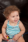 13 month old baby girl at home sitting on couch smiling looking to side vertical