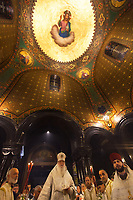 Switzerland. Geneva. Easter at the Russian Church. The church is a lovely 19th-century Russian Orthodox church and designed in a Byzantine Moscovite style. The church's full name is Cathédrale de l'Exaltation de la Sainte Croix. The Archbishop Michael with a mitre during the religious service on the night of Easter Sunday. The nighttime liturgy is a blessing of Easter fire with candles and the celebration of the Easter Proclamation of the Resurrection of Jesus Christ. Deacons hold in hands the Paschal Trikirion which is a liturgical triple-candlestick used at Easter time in the Eastern Orthodox ceremony. It is used from the commencement of the celebration of the Resurrection during the Paschal Vigil. Religious paintings of Jesus Christ with gold leaf used for halo, Apostles and angels. A halo (also known as a nimbus, aureole, glory, or gloriole) is a ring of light that surrounds a person in art. Archbishop Michael (Secular name - Simeon Vasilyevich Donskoff; born on 29 March 1943) is a bishop of the Russian Orthodox Church Outside of Russia, Archbishop of Geneva and Western Europe. Easter, also called Pascha or Resurrection Sunday is a festival and holiday celebrating the resurrection of Jesus from the dead, described in the New Testament as having occurred on the third day of his burial after his crucifixion.The Russian church serves not only the Russian community but also Bulgarians, Serbs, Coptic Christians and other Orthodox worshippers who do not have their own church in Geneva. 16.04.17 © 2017 Didier Ruef