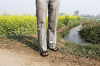 A man stands near farmland on the outskirts of the city of Kanpur. Local water channels are laced with toxins, released from the nearby leather-producing tanneries. The water goes directly onto farmland, feeding into the local food chain, resulting in serious health problems for many locals.