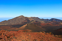 Haleakala's many red and brown cinder cones appear one after another as a hiker progresses along the Sliding Sands Trail, Haleakala National Park, Maui.