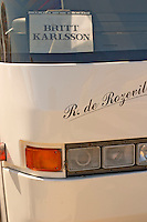 A white tourist bus from R de Rozeville with indicator light and head light taking tourists around Bordeaux