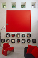 The large wall-mounted red square and rows of small black-framed shelves are the focal point of this living room