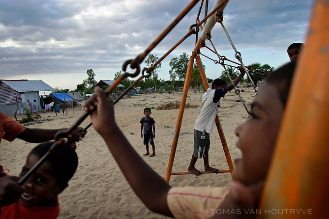 Children play on swings near temporary shelters where homes were destroyed by the tsunami in Kaluanchikoli Suriyaparum, near Batticaloa, Sri Lanka on 15 October, 2005. The area was hit by the tsunami on 26 December 2004.<br />