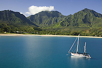 Cruising sailboat in Hanalei Bay with Namolokama Mountain in the background